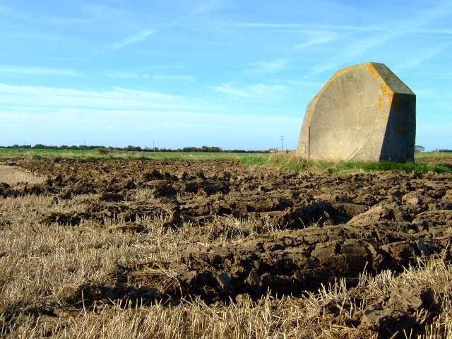 The farmland has been ploughed around the mirror. The rusty pole in front of the mirror had a microphone attached to it when listening for aircraft in WWI. Author:John Poyser CC BY SA2.0