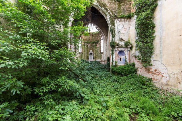A carpet of green rolls out under the arches of a beautiful stone structure. Author: Jonk Photography