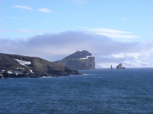 "Entrance to Deception Island with the ""Sewing-machine Needles"". Livingston Island is seen behind and to the right. Author: Pietbarber CC BY-SA 3.0"