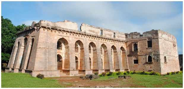 """Hindola Mahal literally means a """"Swinging Palace"""" a name given to its peculiar sloping sidewalls. The plan of the building is 'T' shaped, with a main hall and transverse projection to the northern side. The massive vaulted roof of the hall has disappeared though the row of lofty arches, which once supported it, is still intact. This large audience hall is dated to 15th century AD. Muk.khan CC BY 3.0"""