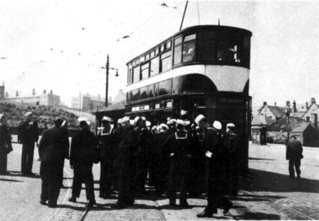 U.S. Navy sailors from the aircraft carrier USS Randolph (CV-15) in front of a double-decker tram in Edinburgh