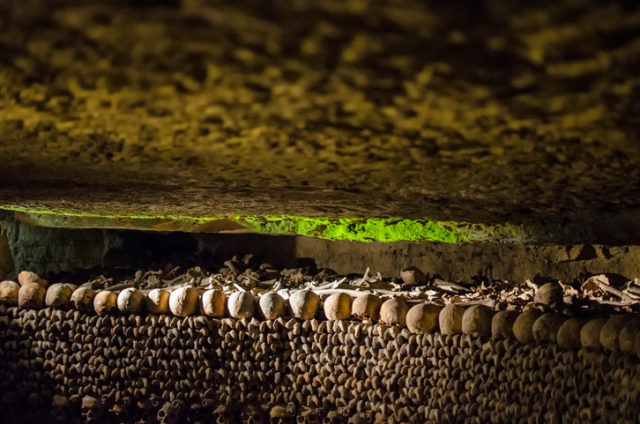 """The Catacombs of Paris are located south of the former city gate and hold the remains of about six million people. The skeletons fill a renovated section of caverns and tunnels that are the remains of historical stone mines, giving it its reputation as """"The World's Largest Grave"""". Opened in the late 18th century."""