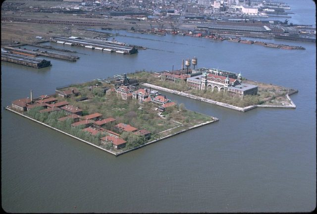 Ellis Island as seen from the air in the early 1970s, with the hospital at the southern (left) side of the island which was created with landfill.