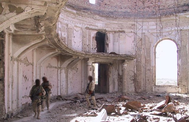 US Commandos patrolling a heavily bombed room in the palace in 2002