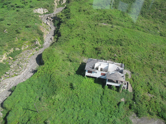 Abandoned home damaged by flying boulders. Author: Leonora (Ellie) Enking CC BY-SA 2.0