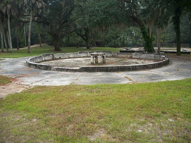 The remains of an ornamental pond, with one of the spa pools visible in the background on the right, and the bridge over Spring Creek to the left. Author: Ebyabe CC BY-SA 3.0