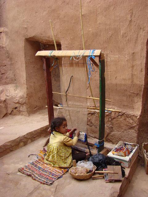 Little girl working on a loom in Aït Benhaddou, May 2008. Author:Zouavman Le ZouaveCC BY-SA 3.0