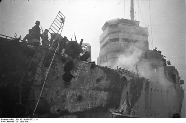 Close up of HMS Campbeltown after the raid. Note the shell damage in the hull and upper works and the German personnel on board the vessel – Author: Bundesarchiv, Bild 101II-MW-3722-19 / Kramer – CC-BY-SA 3.0