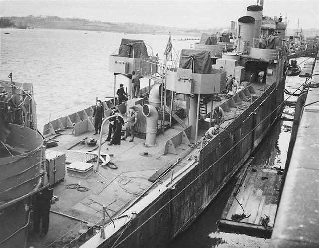 HMS Campbeltown being converted for the raid. There are twin lines of armour plate down each side of the ship and the Oerlikon mountings. Two of her funnels have been removed, with the remaining two cut at an angle.