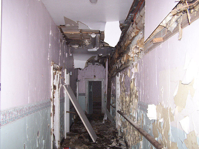 The decaying corridor of the isolation ward. Photo Credit