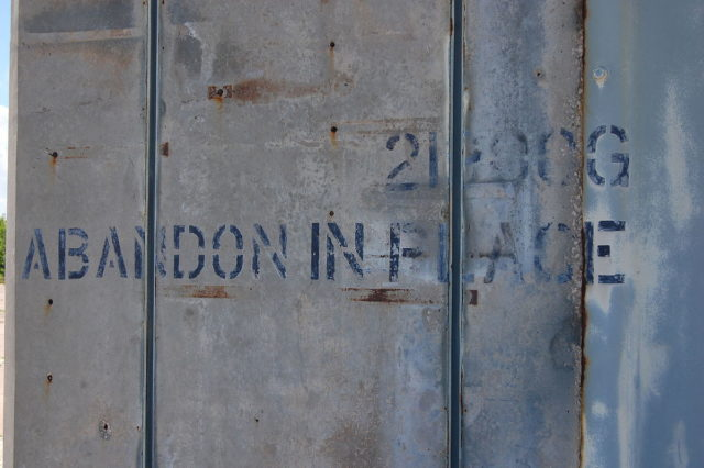 """Abandon in place"" graffiti at Launch Complex 34, meaning to abandon it ""as is"", with no maintenance – Author: Bubba73 – CC BY-SA 3.0"
