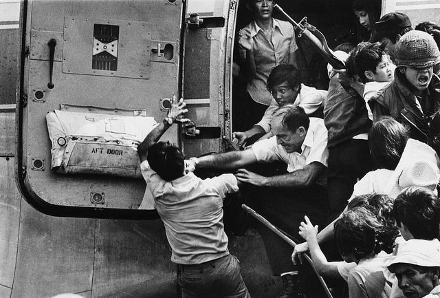 A man trying to board an overloaded evacuation plane is stopped by an American official at Nha Trang Air Base in South Vietnam – Author: manhhai – CC by 2.0