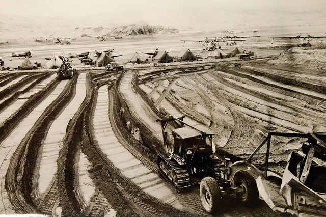 Tractors and grading machines grind out pathways in the stubborn soil of Adak, during the construction of bases on Aleutian strongpoints – Author: National Museum of the U.S. Navy – CC by 2.0
