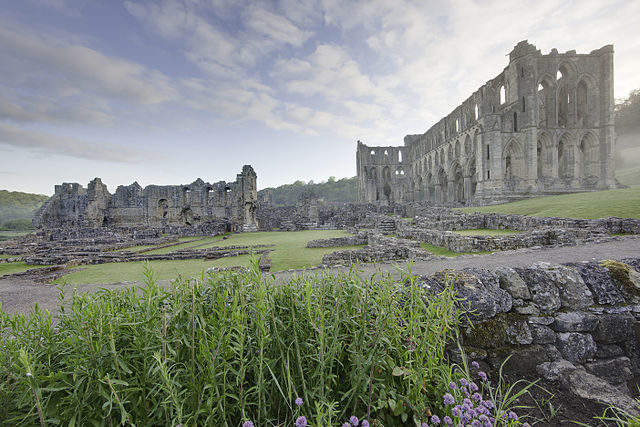 Rievaulx Abbey showing Presbytery (right), South Transept, Chapter House foundations and wall of Infirmary (left). Author: WyrdLight.com – CC BY-SA 3.0