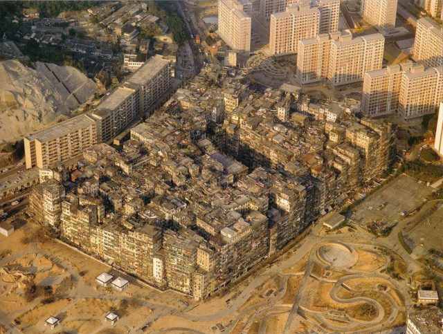 Kowloon Walled City. A large solid block of ramshackle buildings varying in height, with many taller buildings and some mountains in the background. – Author: Ian Lambot – CC BY-SA 4.0
