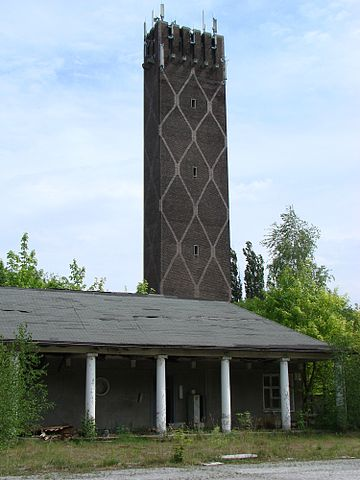 Former Cavalry School Krampnitz. Tower at the entrance (east side) to the military and driving school, 2007 – Author: Elvira Schmidt – CC BY-SA 3.0