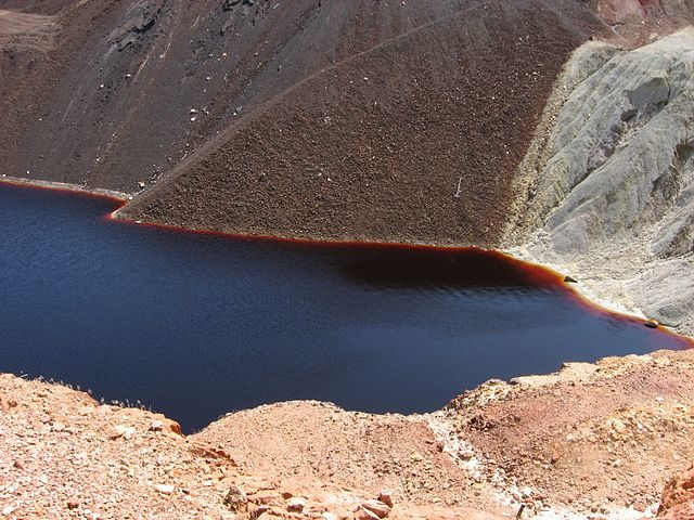 Water in the pit is red due to iron and is acidic from sulfur oxidation – Author: Ceinturion – CC BY 2.5