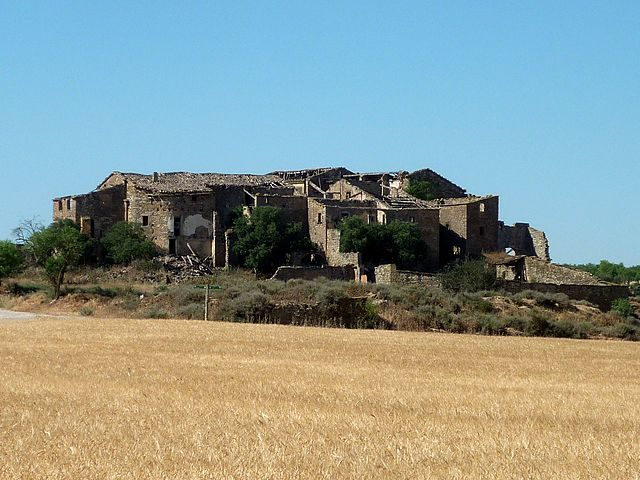 The ruins of Conill are overgrown with vegetation. Author: Isidre blanc – CC BY-SA 3.0