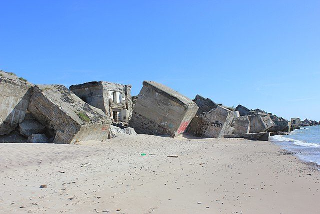 Ruined concrete structures in the sand/ Author: Andrzej Otrębski – CC BY-SA 4.0