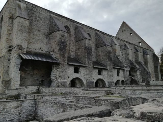 Foundations of several stone buildings next to the imposing Gothic church