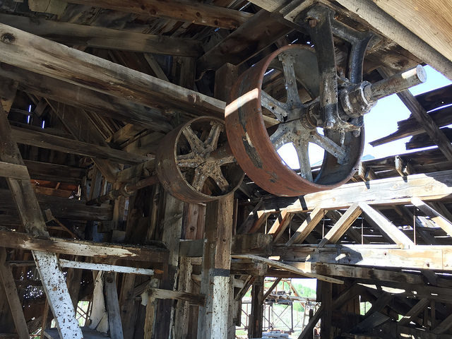 Overhead pulleys and drive shaft in Chemung Mine mill – Author: The Greater Southwestern Exploration Company – CC BY 2.0