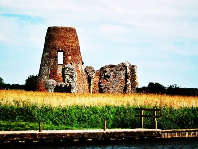 The ruins of the abbey and wharf from the River Bure/ Author: Richard Harvey – CC BY 3.0