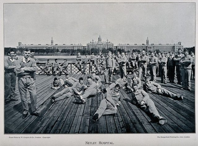 Soldiers relaxing with the hospital in the background. Author: Wellcome Images – CC BY 4.0
