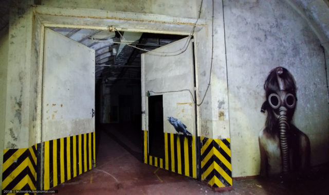 Inside a nuclear warheads store, with street art by Plotbot KEN on the wall and door ©technolirik