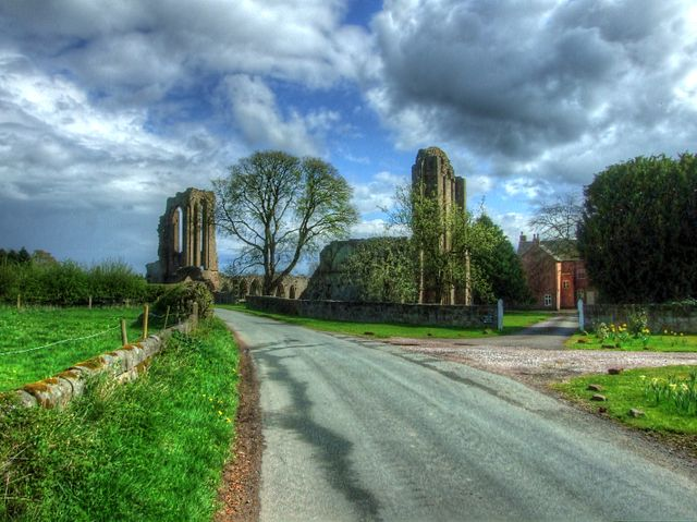 The road through the village cuts through right through the church/ Author: Alun Salt CC BY-SA 2.0