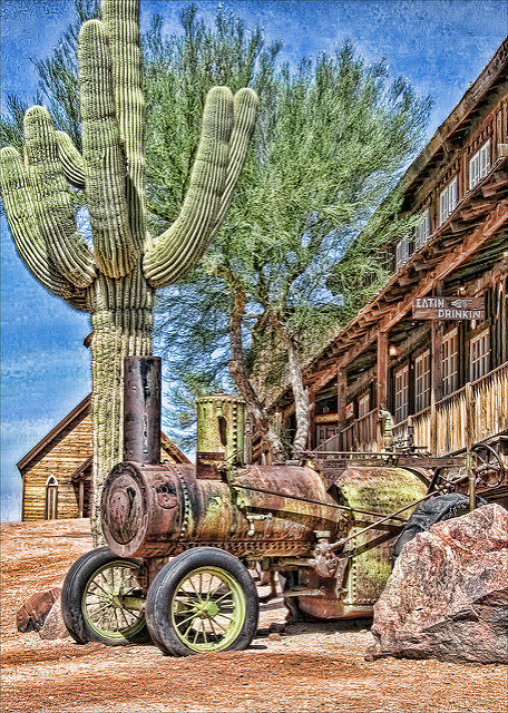 Part of Goldfield with huge Arizona cactus in front of a dinner. Author:ArizonaGlo–CC BY-ND 2.0