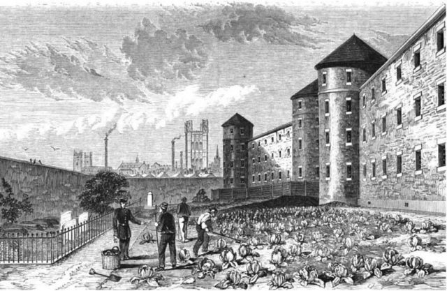 The burial grounds, where prisoners work under the view of guards. Author:Herbert Watkins –Public Domain