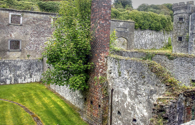 The harsh grays of the remains of the jail are tempered by the encroaching green of nature. Author: psyberartist CC BY 2.0