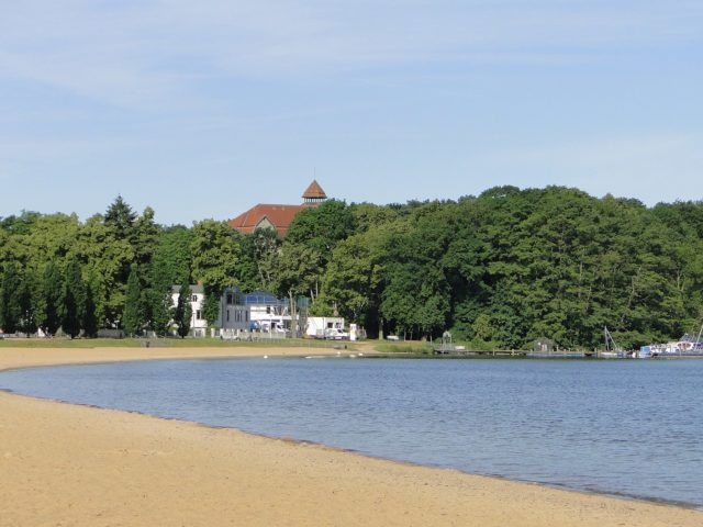 Beach and abandoned hotel in the background. By Niteshift (talk) – CC BY-SA 3.0