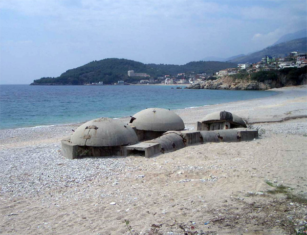 "A ""triple series"" of linked Qendra Zjarri bunkers on an Albanian beach. By Elian Stefa, Gyler Mydyti – Concrete Mushrooms Project, CC BY-SA 3.0"