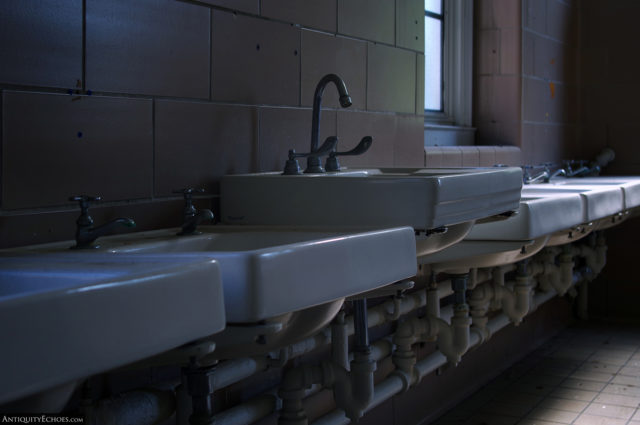 A row of sinks along the brick wall