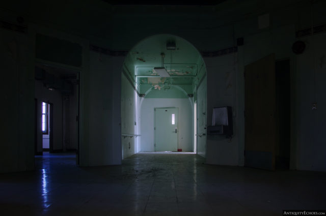 A dark room with a partially lit entrance