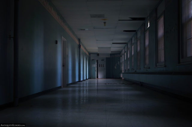 A dark hallway only lit by covered windows