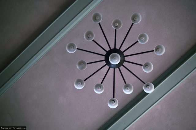 A chandelier on the hospital's pink and mint green ceiling