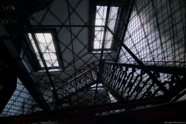 A downward view of a staircase through a gated window