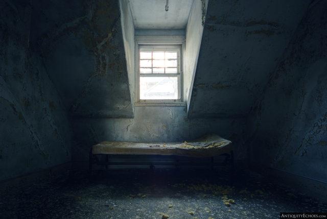 Dirty mattress beneath a window
