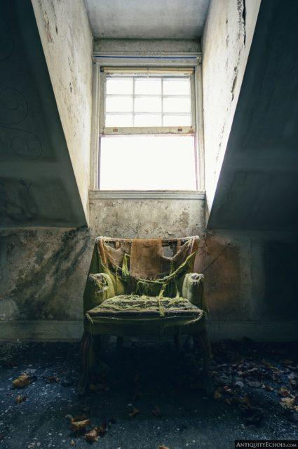 Damaged green chair placed below a window