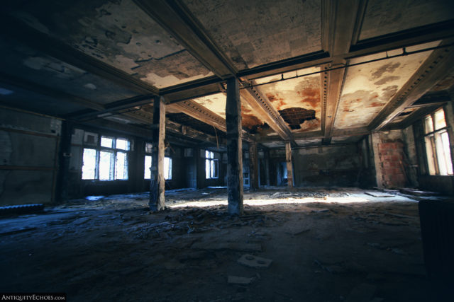 Decaying room with metal beams on the ceiling