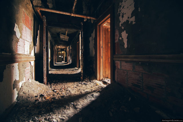 Hallway covered in dirt and with decaying walls