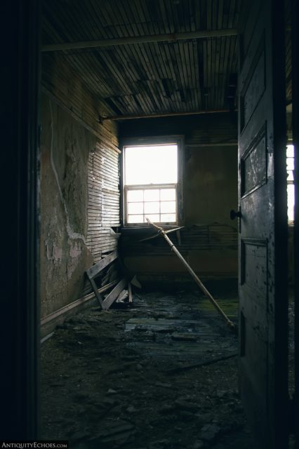 Dilapidated room lit only by a single window