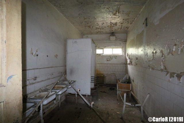 Decaying room with sinks along the wall
