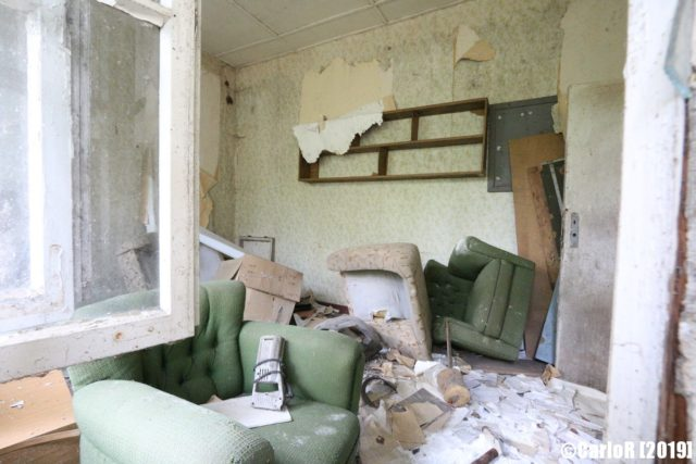 Deteriorating room scattered with debris and old furniture