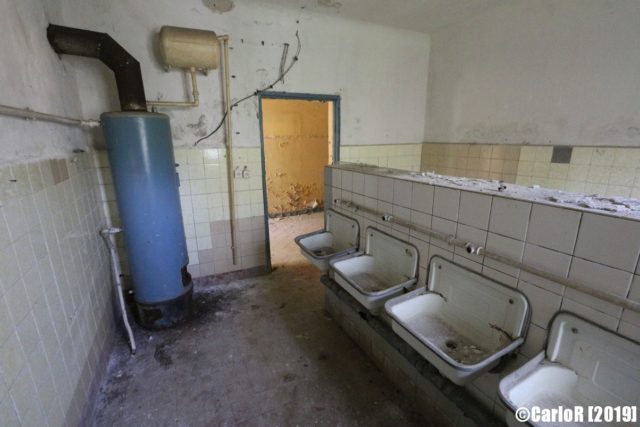 A room with a blue water heater on the left and a row of sinks on the right