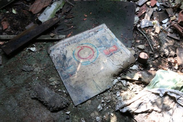 Paper with images on it on the ground, surrounded by debris