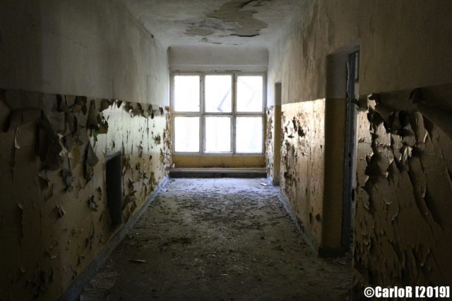 Deteriorated hallway lit by a large window