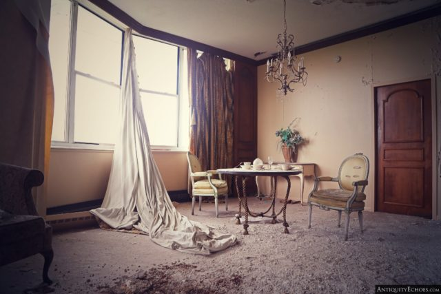 Abandoned room with a table, chairs and curtains hanging from the window